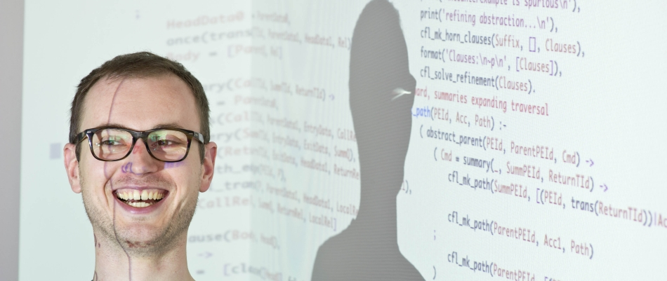 Prof. Dr. Andrey Rybalchenko in front of a projection of programming language