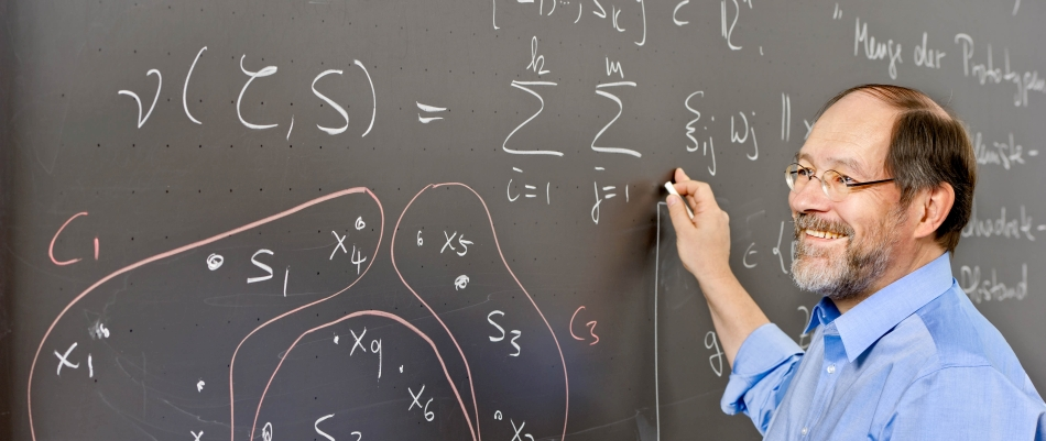 Prof. Dr. Peter Gritzmann writing on a blackboard with mathematical symbols
